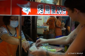 "Getting  the ""quail egg ball stick"" (although maybe they are pigeon eggs because of the picture on the sign?)"